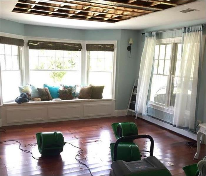 air movers drying hardwood flooring with a removed portion of the damaged ceiling