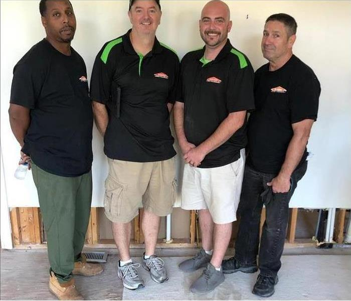 Four SERVPRO employees standing together.