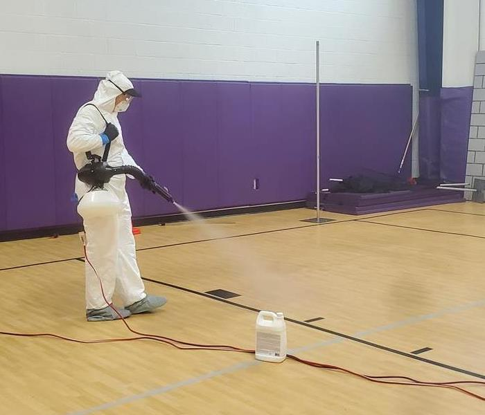 a guy in a white tyvek suit in a gym spraying disinfectant